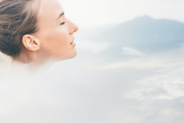 Sport woman relaxing on mountain cliff above the clouds.